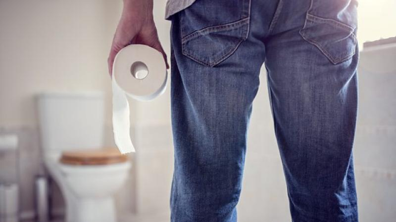 Person standing in front of toilet with toilet paper in hand